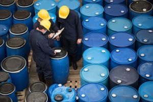 Group of men working at a chemical warehouse classifying barrels