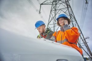 male and female engineers beneath an electricity pylon looking at plans on the bonnet of their van . The female engineer is on the phone.